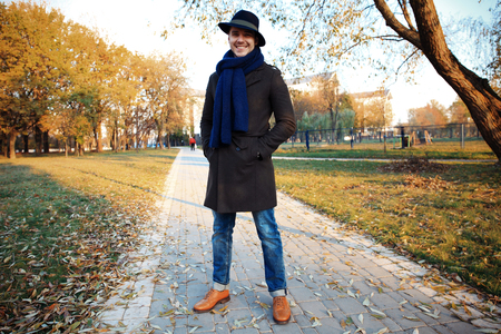 Trendy handsome young man in autumn fashion standing in urban environment.
