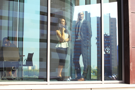 Confident business partners walking down in office building and talking. photo