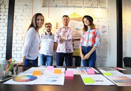 Portret van gelukkige jonge mensen in een vergadering te kijken naar de camera en lacht. Jonge ontwerpers werken samen aan een creatief project Stockfoto