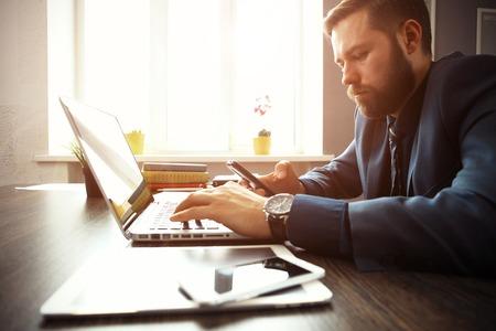 usando computadora: Apuesto hombre de negocios que trabaja con la computadora portátil en la oficina. Foto de archivo