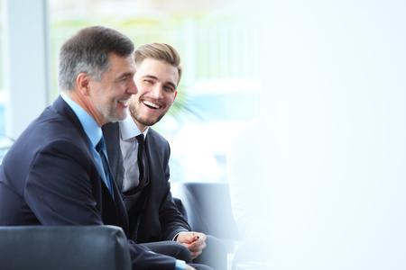 Oudere zakenman met behulp van een digitale tablet om informatie te bespreken met een jongere collega in een moderne business lounge