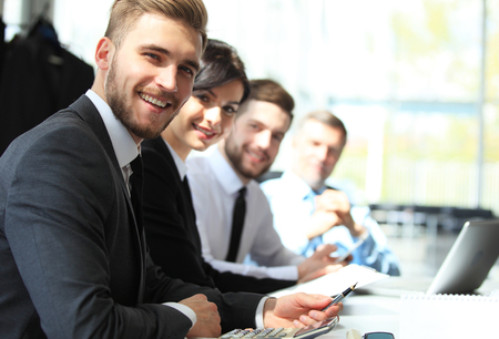 Business people sitting in a row and working, focus on young man
