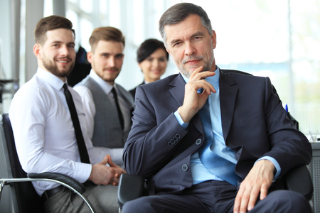 Mature smiling business manager in front of his business team