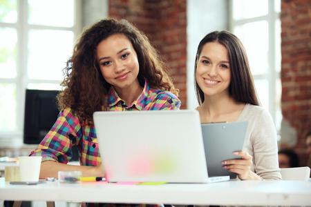 2 つのビジネスの女性の投資コンサルタント会社年次財務報告書貸借対照表ステートメント ドキュメント グラフの操作を分析します。経済、市場、