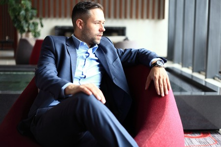 Portrait of a positive young businessman sitting in a modern corporate environment, looking at the camera