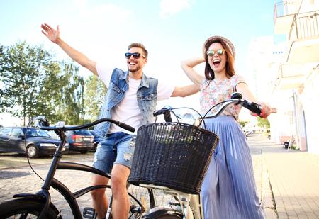 행복 한 젊은 커플 자전거에 대 한가 여름에 도시를 타고. 그들은 재미를 함께 있습니다.
