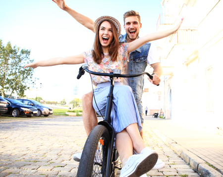 Happy funny young couple riding on bicycle Stock Photo