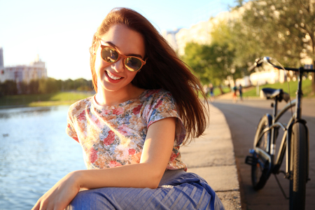 Woman with white teeth thinking and looking sideways in a park in summer