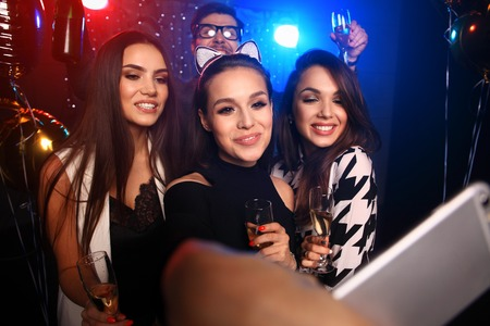 party, technology, nightlife and people concept - smiling friends with smartphone taking selfie in club.