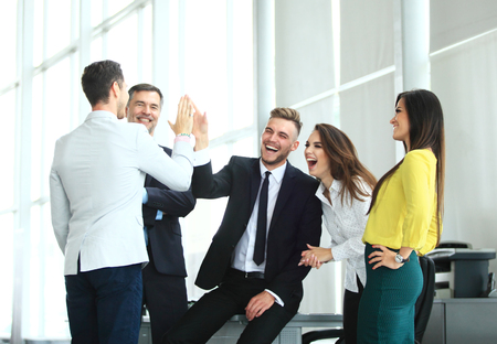 Happy successful multiracial business team giving a high fives gesture as they laugh and cheer their success 版權商用圖片
