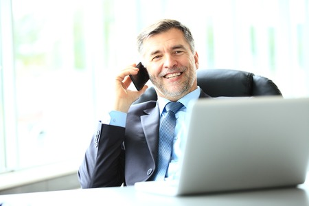 business, people and technology concept - happy smiling businessman with laptop computer office Stock Photo