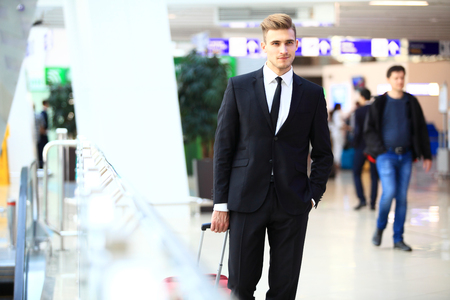 Business man at airport with suitcase