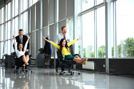 Cheerful colleagues having fun in office chairs.