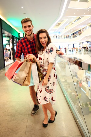 sale, consumerism and people concept - happy young couple with shopping bags walking in mall. Stock fotó - 94756494