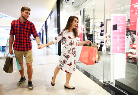 sale, consumerism and people concept - happy young couple with shopping bags walking in mall.