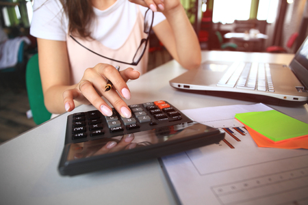 Business and finance concept.women work with calculator and laptop,pen and notebook on the wooden table
