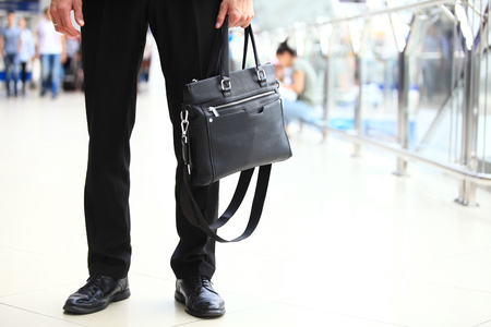 A young handsome businessman student in a suit, comes with a briefcase, at the station, airport. Concept - a new business, traveling the world, communication, contacts, a new deal, success, walk. Standard-Bild - 95040616