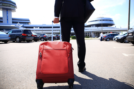 Close-up of businessman carrying suitcase while walking through a passenger boarding bridge Stock Photo