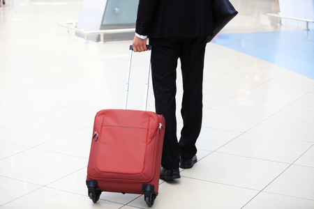 Close-up of businessman carrying suitcase while walking through a passenger boarding bridge Stock Photo - 94916314