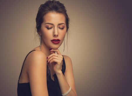 Beautiful model girl with elegant hairstyle . Woman with red lips and nails . Cosmetics, beauty and manicure on nails. Stock Photo
