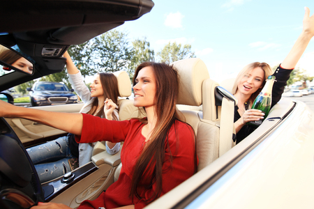 three girls driving in a convertible car and having fun. Stock Photo