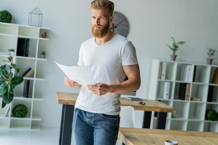 Bearded young businessman working at modern office.Man wearing white t-shirt and making notes on the documents. Banco de Imagens