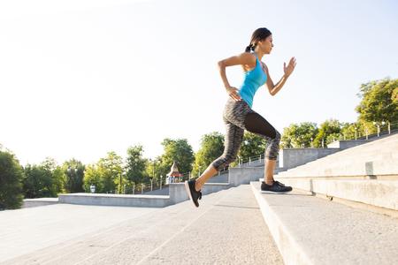 gesunde Frau Sport Frau läuft auf Steintreppen Sonnenaufgang Meer