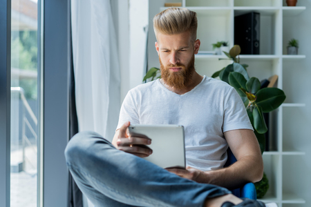 Multitasking. Handsome young man wearing glasses and working with touchpad while sitting on the couch in office Stock Photo