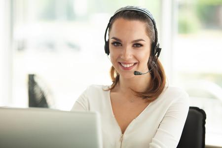 Operador de soporte al cliente femenino con auriculares y sonriendo.