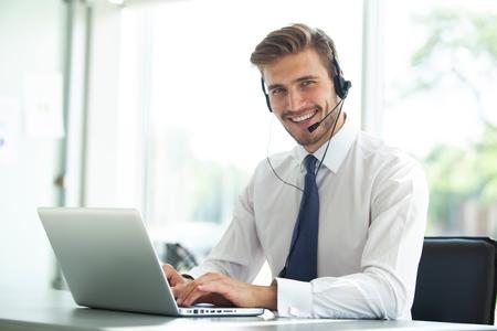 Felice giovane maschio dirigente del servizio clienti che lavora in ufficio.