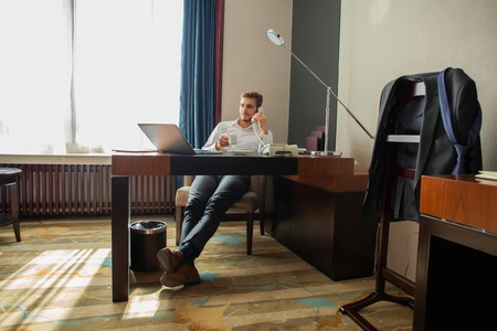 Portrait of handsome young entrepreneur speaking by phone and using laptop while working in comfortable hotel room or office.