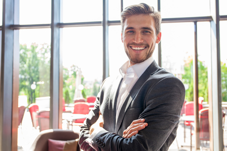 Portrait of happy businessman with arms crossed standing in office. 写真素材