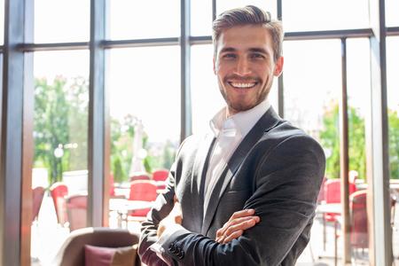 Retrato de hombre de negocios feliz con los brazos cruzados de pie en la oficina. Foto de archivo