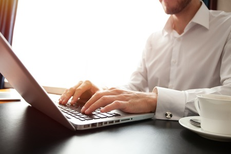 Business man using laptop computer. Male hand typing on laptop keyboard. Imagens
