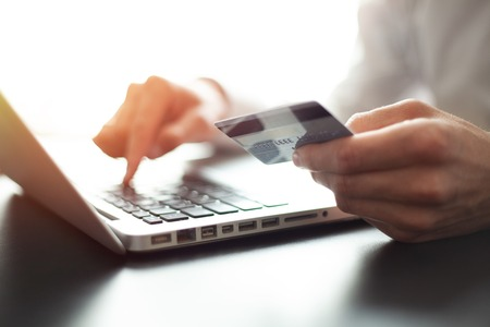 Hands holding credit card and using laptop. Online shopping.