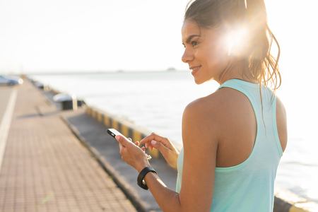 Tired fitness woman sweating taking a break listening to music on phone after difficult training. Stock Photo