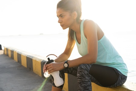 Portrait of tired fitness young woman outdoors in the city Stock Photo