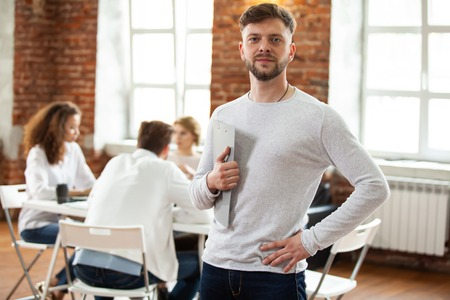Confident team leader. Confident young man keeping arms crossed and looking at camera with smile while his colleagues working in the background.