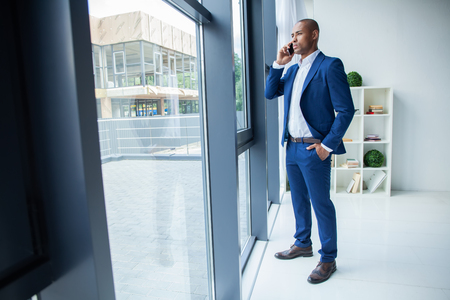 Black American Businessman Standing at the window, Calling Someone Through Mobile Phone. Stok Fotoğraf