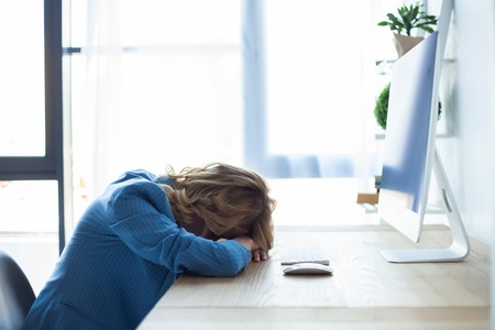 Tired businesswoman sleeping on the desk, in front of the computer screen