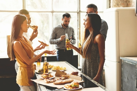 Home party. Full length of cheerful young people enjoying home party while communicating and eating snacks on the kitchen. Stock Photo