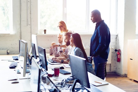 Creative office. Young modern colleagues in smart casual wear working while spending time in the office. Stock Photo