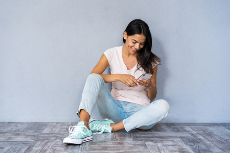 Happy brunette woman sitting on the floor and writing message on smartphone over gray background.