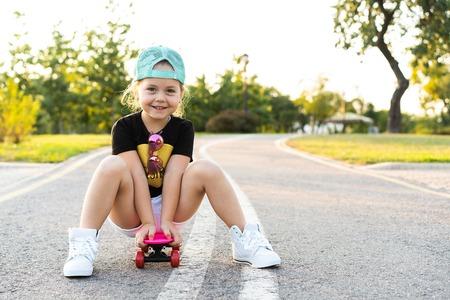 Moda niña sentada en patineta en la ciudad, con gafas de sol y camiseta.