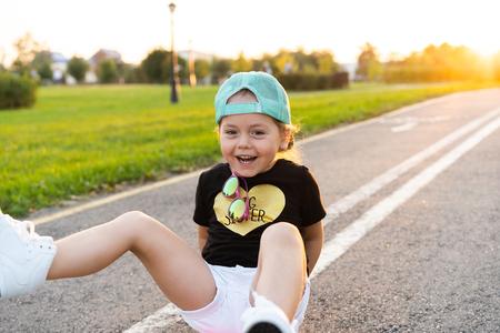 Child riding skateboard in summer park. Stock Photo