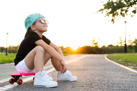 Fashion little girl child sitting on skateboard in city, wearing a sunglasses and t-shirt.
