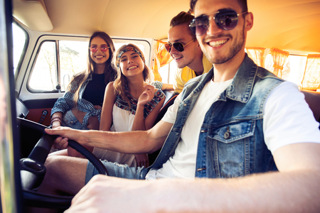 Enjoying great roadtrip with friends. Group of cheerful young people having fun while sitting inside of minivan. Banco de Imagens - 109828754