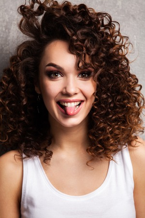 Portrait of beautiful cheerful girl with flying curly hair smiling laughing looking at camera over gray background.