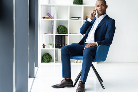 handsome african american businessman talking on mobile phone in modern office.