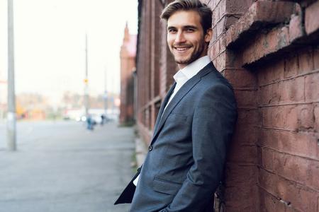 Glimlachend jonge mannelijke manager formeel gekleed leunend op een muur buitenshuis.